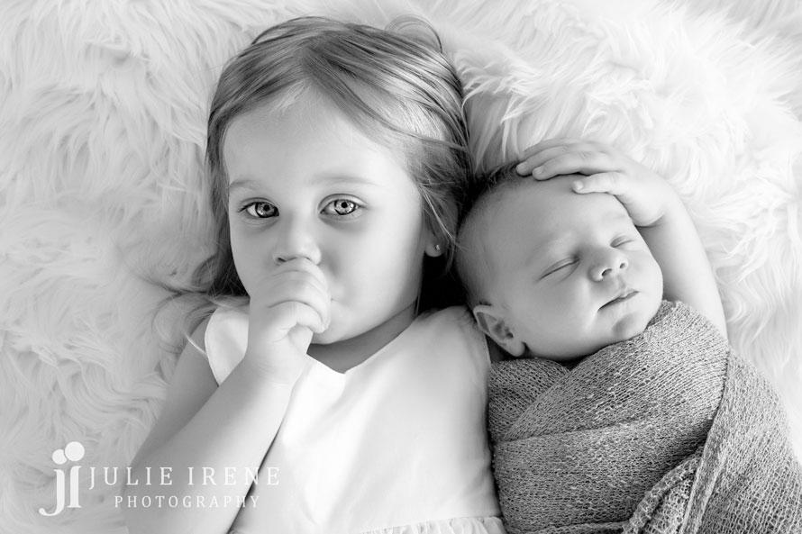 sister and newborn baby boy sucking thumb