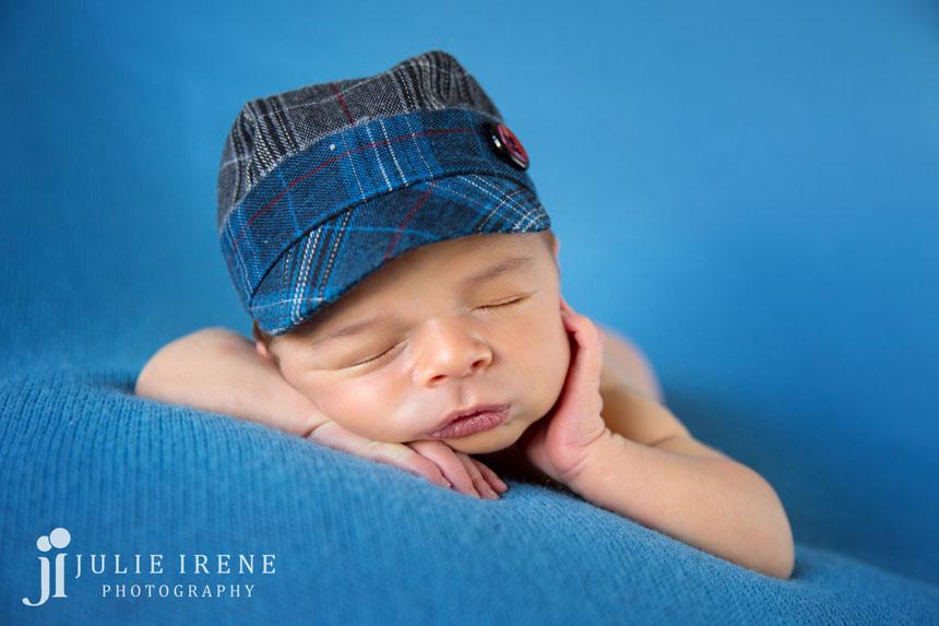 cute hat newborn baby hand on cheek blues photo